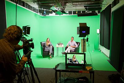 Woman and man sitting in front of a green screen.