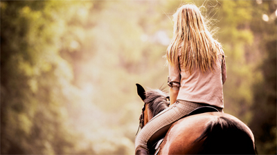 Women riding a horse on a trail.
